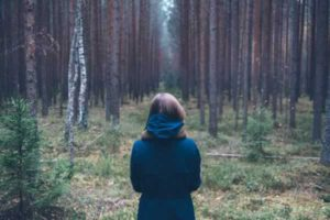woman in a coat in the forrest